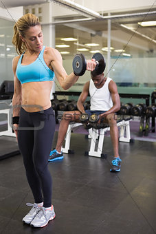 Fit woman exercising with dumbbell in gym