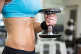 Mid section of fit woman exercising with dumbbell in gym