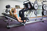 Side view of fit woman doing leg presses in gym