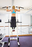 Rear view of fit woman doing pull ups at gym
