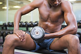 Mid section of shirtless muscular man exercising with dumbbell in gym