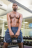 Shirtless muscular man lifting kettle bell in gym