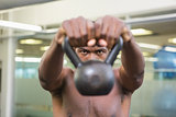 Close-up portrait of shirtless man lifting kettle bell