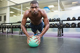 Determined man doing push ups with ball in gym