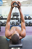 Shirtless man exercising with dumbbell in gym