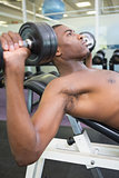 Shirtless young man exercising with dumbbells in gym