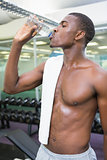 Shirtless man drinking water at gym