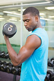 Side view of young man exercising with dumbbell in gym