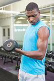 Side view of man exercising with dumbbell in gym