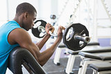 Determined muscular man lifting barbell in gym
