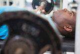Determined young man lifting barbell in gym