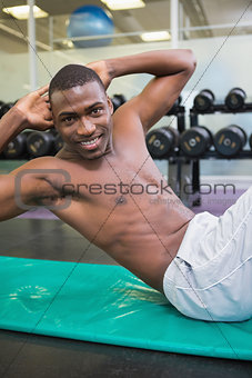 Portrait of shirtless man doing abdominal crunches in gym