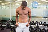 Shirtless man lifting barbell in gym