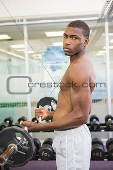 Portrait of serious man lifting barbell in gym
