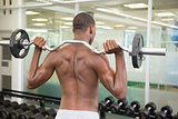 Rear view of shirtless man lifting barbell in gym