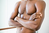 Mid section of shirtless man with arms crossed