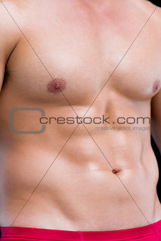 Close-up mid section of a shirtless muscular man