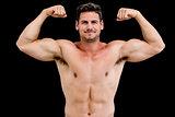 Portrait of shirtless muscular man flexing muscles