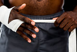 Mid section of a man binds bandage on hand