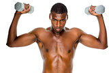 Determined fit shirtless man lifting dumbbells