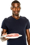 Portrait of smiling young man holding a plate of raw meat