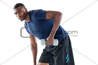 Portrait of casual young man lifting dumbbell
