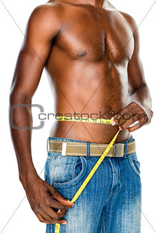 Mid section of a fit shirtless man measuring waist