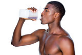 Side view of a sporty man drinking protein