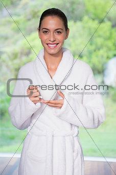 Beautiful woman in bathrobe having tea outdoors