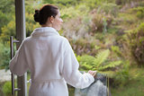 Woman wearing bathrobe against blurred plants