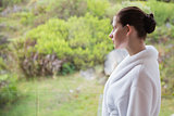 Woman wearing bathrobe against blurred plants