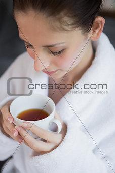 Beautiful woman in bathrobe having tea