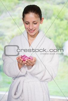 Beautiful woman in bathrobe holding flowers