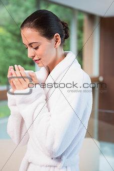 Beautiful young woman in bathrobe having tea