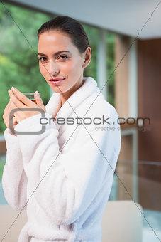 Portrait of woman in bathrobe having tea