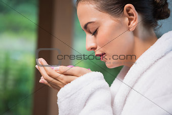 Beautiful woman smelling flowers in spa