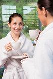 Women in bathrobes having tea
