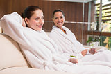 Smiling women in bathrobes sitting on couch