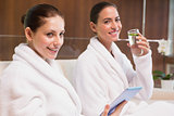 Women in bathrobes drinking water and text messaging