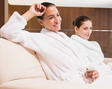 Smiling women in bathrobes drinking water
