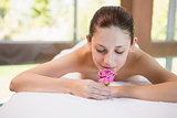 Beautiful woman holding flower on massage table at spa center