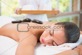 Beautiful woman receiving stone massage at health farm
