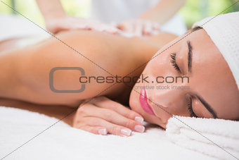 Attractive woman receiving back mask cream at spa center