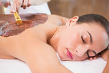 Attractive woman receiving chocolate back mask at spa center