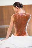 Attractive woman with chocolate back mask at spa center