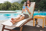 Woman reading book on sun lounger by pool