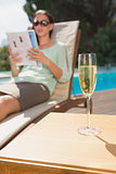 Woman reading book by pool with champagne in foreground