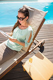 Woman reading book by swimming pool with champagne on table