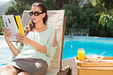 Woman reading book by pool with breakfast on table