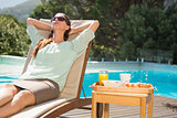 Woman relaxing by pool with breakfast on table